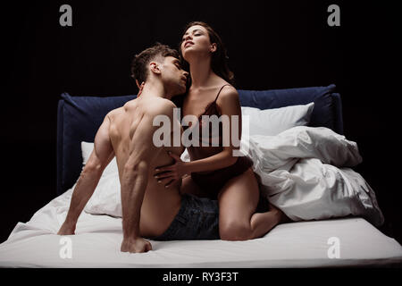 young sexy couple passionately embracing in bed isolated on black - Stock Image