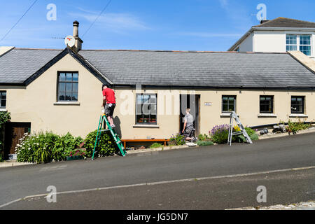 Two men painters painting a picturesque cottage on a steep hill road. - Stock Image