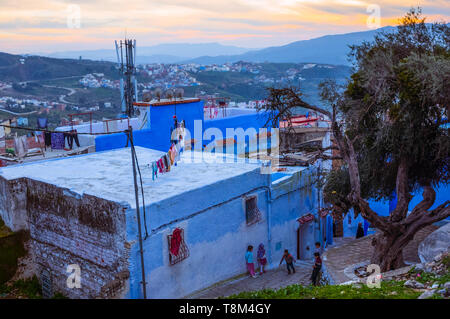 Chefchaouen, Morocco : General view at dusk of the blue-washed medina old town with children playing in the street. - Stock Image