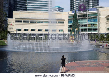 Tourist photographing the lake and fountains at Kuala Lumpur City Centre KLCC: Malaysia. - Stock Image