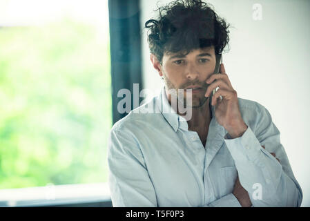 Businessman talking on smartphone - Stock Image
