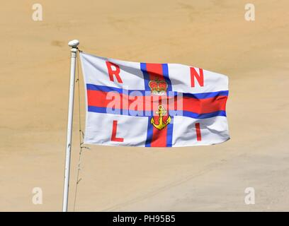 Royal National Lifeboat Institution flag,RNLI ensign flag against a sandy beach back ground - Stock Image