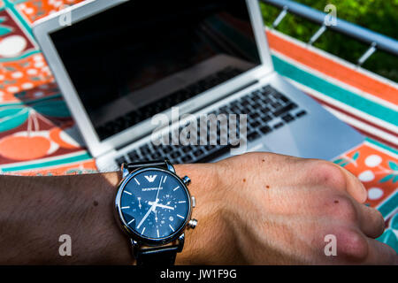 View from person's eyes. Checking hour on a Giorgio Armani watch with a notebook laying on a sunbed in the background. - Stock Image