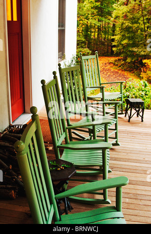 Green rocking chairs on front porch of white rural farmhouse - Stock Image