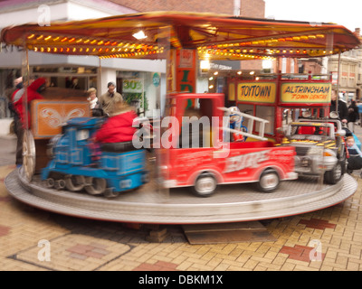 Childrens rides on street carousel in Altrincham Market - Stock Image