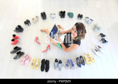 Brunette woman at her home surrounded by shoes. - Stock Image