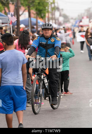 Police officer on a bicycle patrols street during the annual Washington's Birthday Celebration parade in downtown Laredo, Texas, USA. - Stock Image