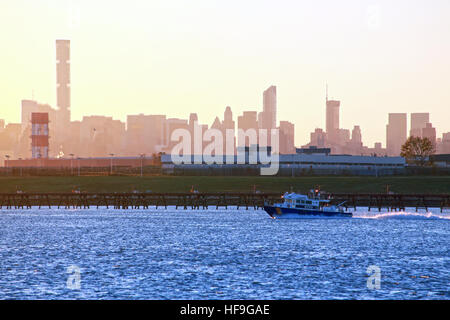 NYPD boat patrolling the East River near Rikers Island jail at dusk, New York, NY, USA - Stock Image