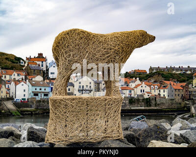 A large osier sculpture of a Polar Bear by Whitby sculptor Emma Stothard on the rock wall in Staithes Harbour Yorkshire during the annual art festival - Stock Image