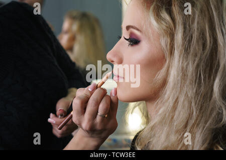 Make-up artist working in a make-up studio, applying makeup on the face of female clients. Makeup artist applies lipstick with a pencil. Evening make- - Stock Image