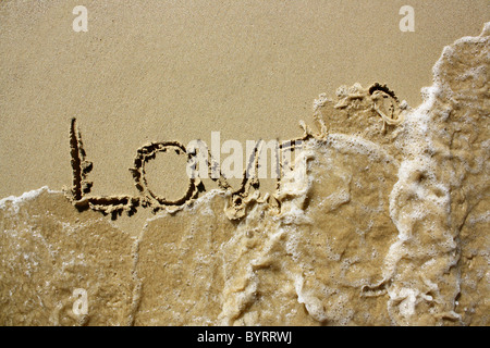 'Love' written out in wet sand, being washed away by the sea. Please see my collection for more similar - Stock Image