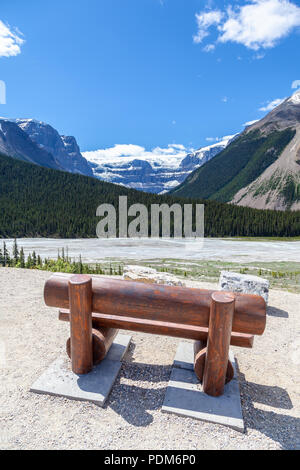 A park bench for visitors to enjoy the view of the Stutfield Glacier on the Icefields Parkway in the Canadian Rockies. The glacier flows southeast fro - Stock Image