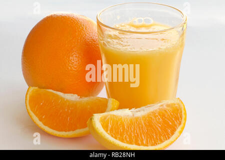 A glass of orange juice with a whole orange and two orange wedges on a white background. - Stock Image