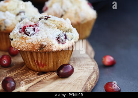Cranberry Muffins with lemon sugar topping on a rustic cutting board with loose berries. Extreme shallow depth of field with selective focus on muffin - Stock Image