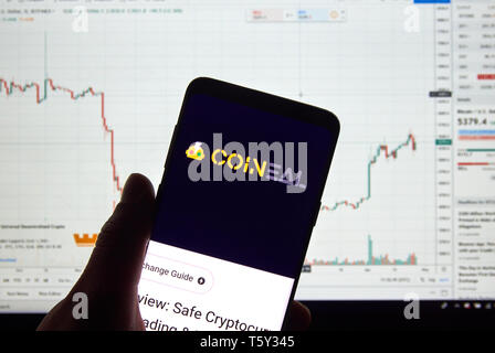 MONTREAL, CANADA - APRIL 26, 2019: Coineal cryptocurrency exchange logo and application on Android Samsung Galaxy s9 Plus screen in a hand over a lapt - Stock Image