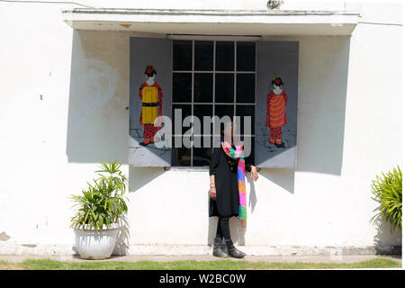 A young beautiful Indian woman in black dress model having fun and posing in front of the window of a Chinese cafe with graffiti artwork on the wall. - Stock Image