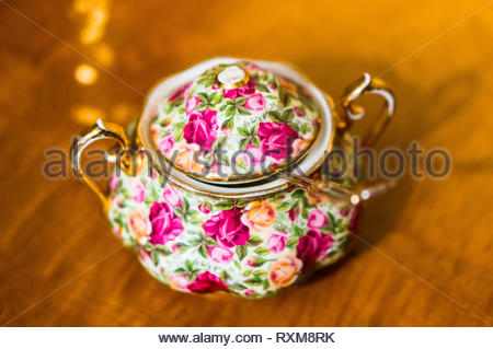 Stylish sugar pot with flower pattern and a gold spoon standing on a wooden surface in soft focus background. - Stock Image