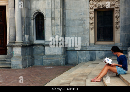USA, Massachusetts, Boston.  A tourist sits on the steps toThe Mother Church, The First Church of Christ, Scientist, - Stock Image