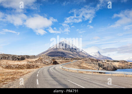 The Iceland Ring Road in South Iceland passing through snowy mountain scenery. - Stock Image