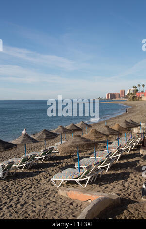 Sun loungers and wicker sunshades on the beach at Benalmadena, Spain. - Stock Image