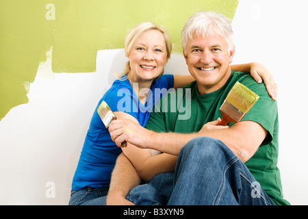 Middle aged couple snuggling in front of wall they are painting green - Stock Image