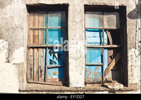 A broken, boarded up window in an old house - Stock Image