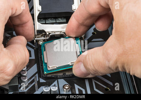 Detail of expert hands at processor replacement. Installation of central processing unit into a socket on computer mainboard. PC hardware maintenance. - Stock Image
