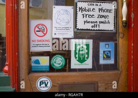 Assorted  signs on the door of an alternative restaurant in Totnes, Devon - Stock Image