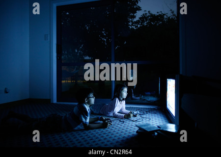 Lit by the screen, boy and girl play video games. - Stock Image