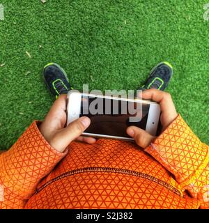 Young boy playing with a smartphone outside - Stock Image