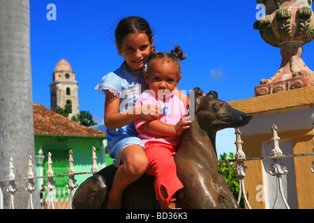 Cuba Trinidad Two girls on a metal greyhound in colonial plaza Photo CUBA0936 Copyright Christopher P Baker - Stock Image