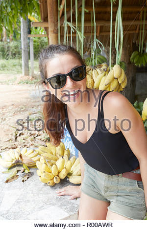 Young woman wearing sunglasses smiling by bananas - Stock Image