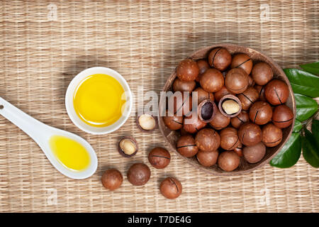 macadamia nuts in a bowl, macadamia oil in a white bowl on a straw (bamboo) background. view from above - Stock Image