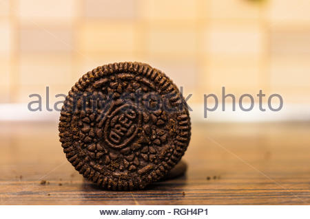 Poznan, Poland - January 25, 2019: Circle shaped Oreo biscuit standing on a wooden table in soft focus. - Stock Image