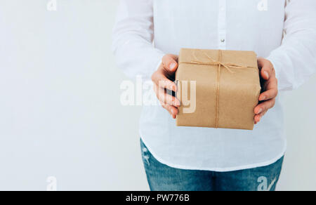 Young caucasian woman in jeans shirt holds in hands gift box wrapped in brown craft paper tied with twine. White wall. Christmas New Years corporate p - Stock Image
