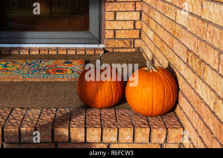 Two mid-sized pumpkins, Cucurbita pepo or winter squash, sitting on the porch of a brick home, used for decor in autumn. Wichita, Kansas, USA. - Stock Image