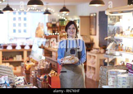 Portrait Of Smiling Female Owner Of Delicatessen Shop Wearing Apron Holding Loaf Of Bread - Stock Image