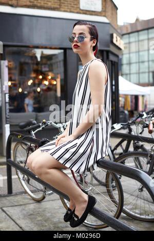 Woman in striped A-line minidress sitting on bike rack - Stock Image