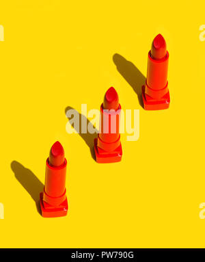 Three red crimson lipsticks arranged in diagonal on solid yellow background. Bright sunlight strong shadows. Creative minimalist funky style pop art.  - Stock Image