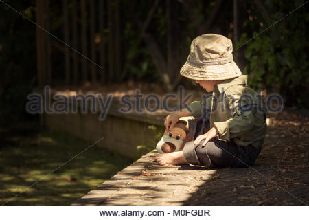 Little boy sitting on wooden porch with his toy pet - Stock Image