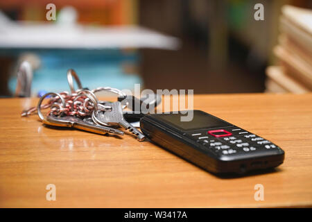 Push-button phone and a bunch of keys on wooden table - Stock Image