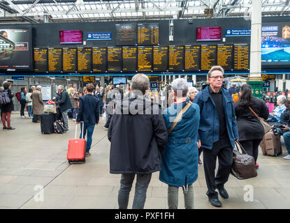 Passengers waiting and arriving in front of the Departures board at Waverley Railway Station, Edinburgh, Scotland, UK - Stock Image