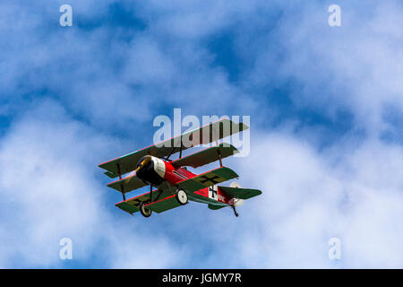 Flying military german triplane Fokker Dr-1 M replica between the clouds. - Stock Image