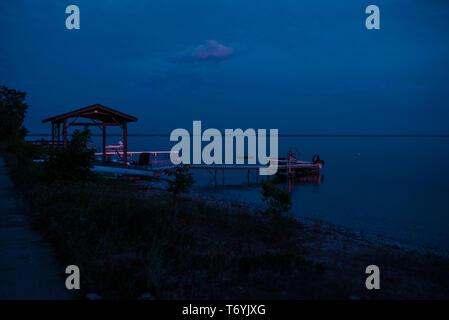Pink reflection of sunset on dock in Lake Michigan - Stock Image