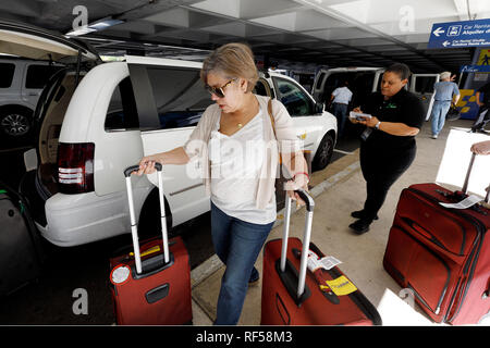 Woman traveler with luggage taxi cab, arrivals, Luis Muñoz Marín International Airport, San Juan, Puerto Rico - Stock Image