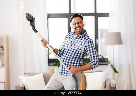 man in headphones with vacuum cleaner at home - Stock Image