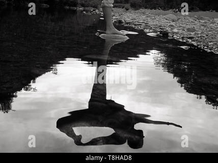 Woman performing yoga on a rock in a mountain river - Stock Image
