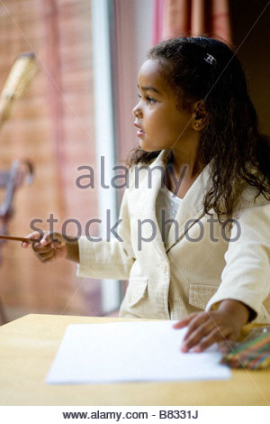 Young black girl aged 4 5 looking right playing with crayons and drawing - Stock Image