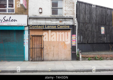 A boarded-up contact lens shop front in Fulham, London, UK - Stock Image