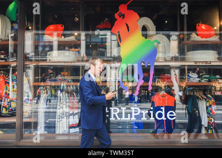 London, UK. 21st June, 2019. A pedestrian walks past a Ralph Lauren shop front decorated with rainbow flags in preparation for the annual Pride celebration and LGBT equality and tolerance Credit: amer ghazzal/Alamy Live News - Stock Image